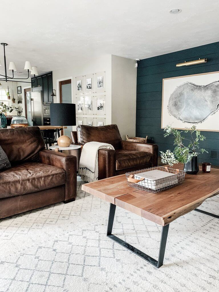 A living room painted in two colors: dark green and off-white