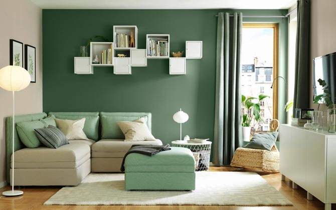 A living room painted in two colors: green and beige