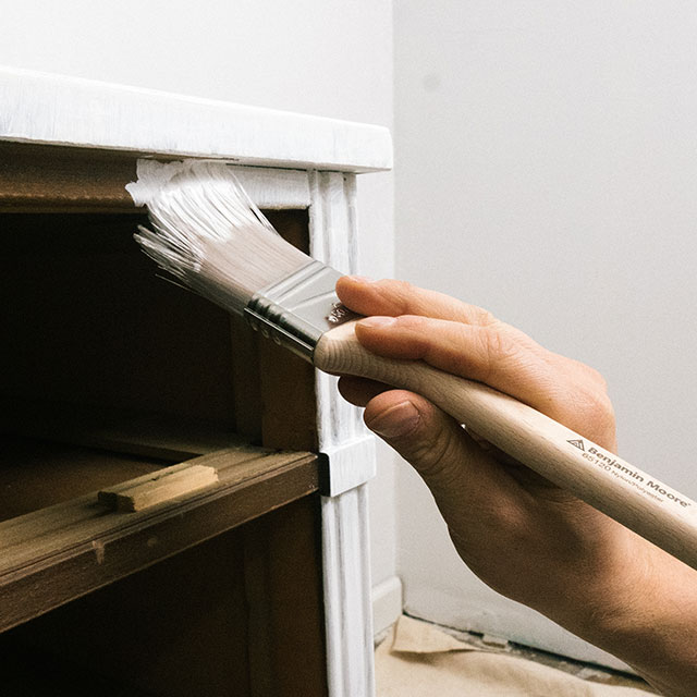 Applying a primer to the surface of a dresser in a room with white walls.